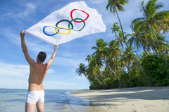 Athlete Holding Olympic Flag Brazilian Beach. BAHIA, BRAZIL - MARCH 18, 2015: Athlete stands on rustic Brazilian beach holding Olympic flag in the wind Stock Photography