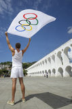 Athlete Holding Olympic Flag Rio de Janeiro. RIO DE JANEIRO, BRAZIL - MARCH 6, 2015: Athlete holding Olympic flag stands outdoors in the plaza above the famous royalty free stock photos