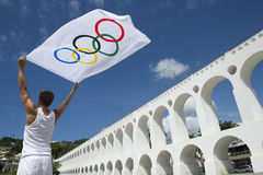 Athlete Holding Olympic Flag Rio de Janeiro. RIO DE JANEIRO, BRAZIL - MARCH 6, 2015: Athlete holding Olympic flag stands outdoors in the plaza above the famous stock photos