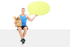 Athlete holding a speech bubble and grocery bag Stock Photography