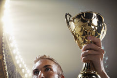Athlete holding trophy cup at night. Athlete holding trophy cup in stadium stock photography