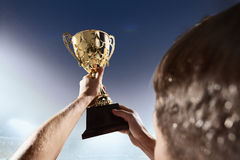 Athlete holding trophy cup at night. Athlete holding trophy cup in stadium royalty free stock images