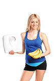 Athlete holding a weight scale and bananas Royalty Free Stock Image