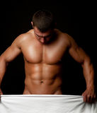 Athlete holding white towel. Naked muscular male holding a white towel as cover Royalty Free Stock Photos