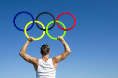 Athlete Holds Olympic Rings Blue Sky. RIO DE JANEIRO, BRAZIL - FEBRUARY 4, 2015: Athlete holds Olympic rings aloft against bright blue sky Royalty Free Stock Photo