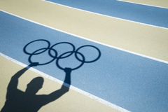 Athlete Holds Olympic Rings Running Track Royalty Free Stock Photos