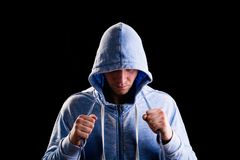 Athlete in the hood holding a jump rope. Jumping rope stock image