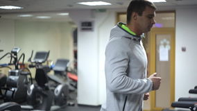 Athlete in a hoodie, engage is on a treadmill in gym. Running is a type of cardio is most popular, and really is addictive in best sense of word. During stock video footage