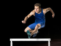 Athlete in hurdling. Male young athlete running over hurdle in track and field Stock Images