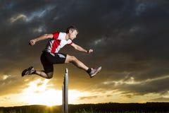 Athlete in hurdling. In sundown Royalty Free Stock Photos