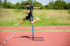 Athlete jumping above the hurdle. During the race Stock Images