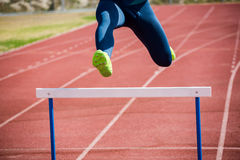 Athlete jumping above the hurdle. During the race Royalty Free Stock Image