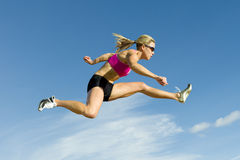 Athlete Jumping Against a Sky Backdrop. Female hurdler jumps against a blue sky in the background Stock Photos