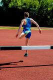 Athlete jumping over the hurdle Stock Photography