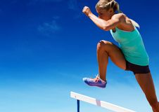 Athlete jumping over hurdles against sky in background Royalty Free Stock Image