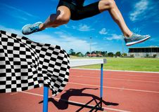 Athlete jumping over hurdles at the finish line Stock Photography