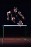 Athlete jumping over a hurdles Stock Images