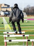 Athlete jumping over hurdles during practice stock photo