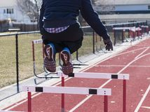 Athlete jumping over hurdles on a track Royalty Free Stock Images