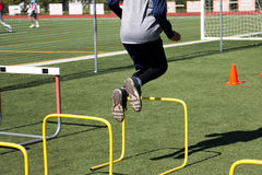 Athlete jumping over yellow hurdles Stock Image