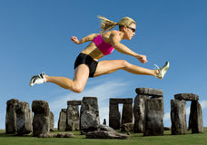 Athlete Jumps Over Stonehenge. Track and field athlete hurdles over Stonehenge Stock Photos