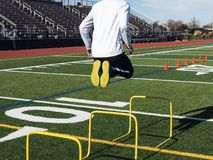 Athlete jumps over yellow hurdles making it look easy Stock Photo