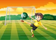 An athlete kicking ball with the flag of Pakistan Stock Images