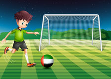 Athlete kicking ball with flag of United Arab Royalty Free Stock Photography