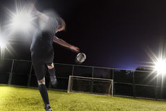 Athlete kicking soccer ball into a goal royalty free stock photography
