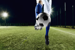 Athlete kicking a soccer ball. Athlete kicking soccer ball at night royalty free stock photography