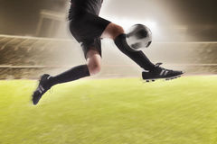 Athlete kicking a soccer ball. Athlete kicking soccer ball at night in stadium Stock Images
