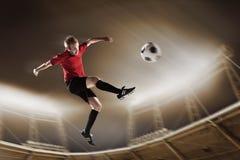 Athlete kicking soccer ball in stadium. At game stock image