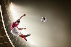 Athlete kicking soccer ball in stadium. At game Stock Photos