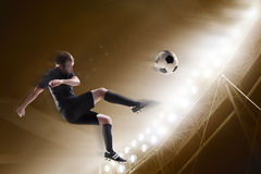 Athlete kicking soccer ball in stadium stock photography