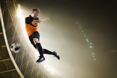 Athlete kicking soccer ball in stadium. At night Royalty Free Stock Images