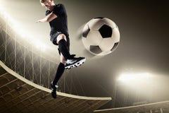 Athlete kicking soccer ball in stadium. At night stock photos