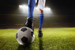 Athlete kicking soccer ball in stadium. At night Royalty Free Stock Photography
