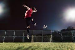 Athlete kicking soccer ball towards goal Stock Photos