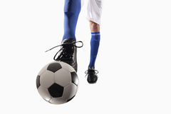 Athlete kicking a soccer ball. Athlete kicking soccer ball on white background royalty free stock image