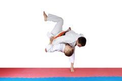Athlete in kimono is throwing athlete with orange belt Stock Photos