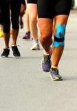 Athlete with knee bandaged by medical bandage during the Maratho Royalty Free Stock Image