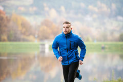 Athlete at the lake running against colorful autumn nature. Young athlete in blue sports jacket at the lake running against colorful autumn nature Stock Photography