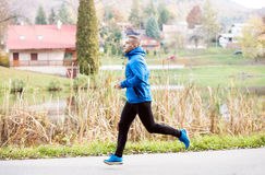 Athlete at the lake running against colorful autumn nature Stock Photos