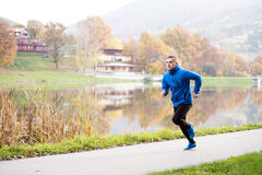 Athlete at the lake running against colorful autumn nature. Young athlete in blue sports jacket at the lake running against colorful autumn nature Stock Image
