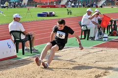 The athlete lands in the sand Royalty Free Stock Photography
