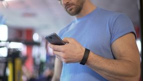 Athlete launching application on smartphone to synchronize with fitness bracelet. Stock footage stock video