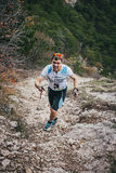 Athlete leader of race up mountain on track Stock Photography