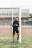 Athlete leaned on the goalpost, listening to music. Royalty Free Stock Image
