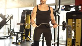Athlete lifting heavy barbell, warming muscles, bodybuilder power and endurance royalty free stock photography