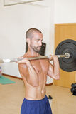 Athlete lifting weights. An athlete lifting weights at the gimnasium Royalty Free Stock Images